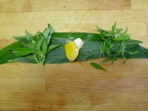 Curry spices: on top of sliced turmeric leaf and cardamom leaf (bottom) is fresh turmeric root (yellow), lemon basil (left) and native mint Mentha satureioides (right)